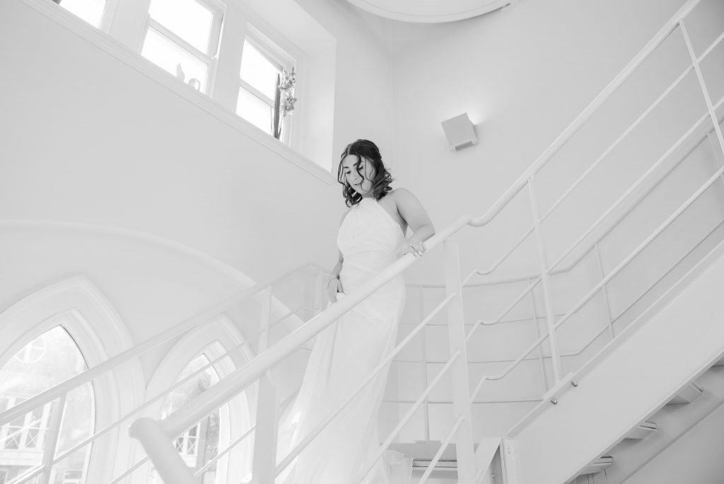 The bride comes down the stairs at St Albans Registry Office