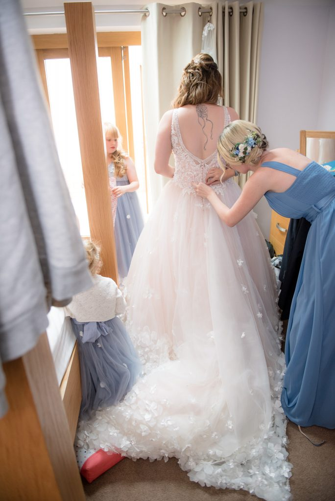 A bride helps with doing up the wedding dress