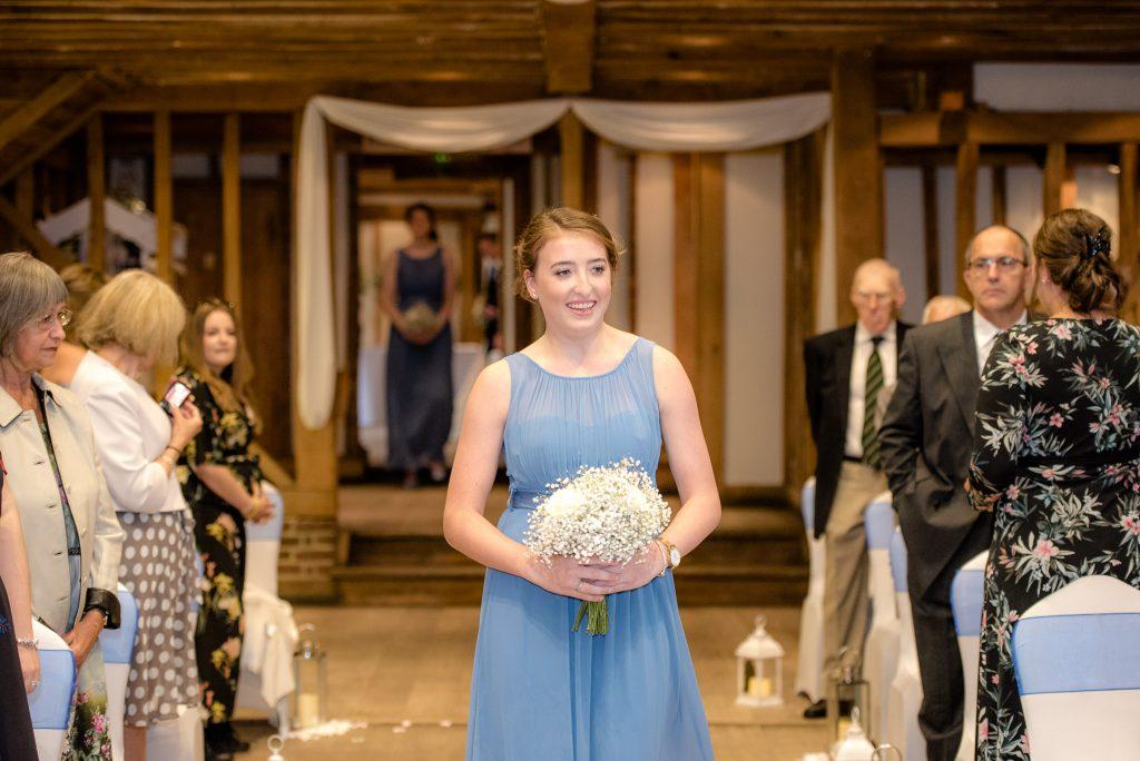 A bridesmaid walks up the aisle