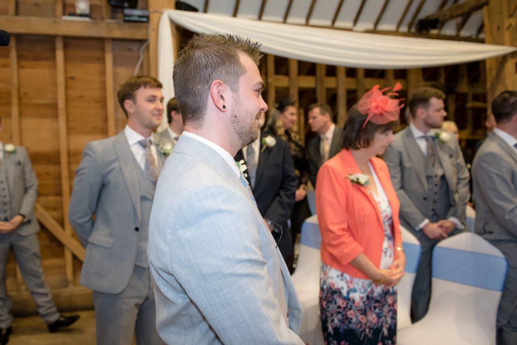 The groom looks around to his bride