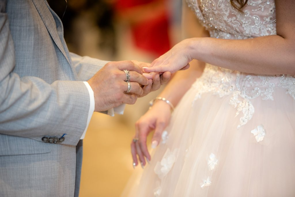 The groom places the wedding ring onto his bride