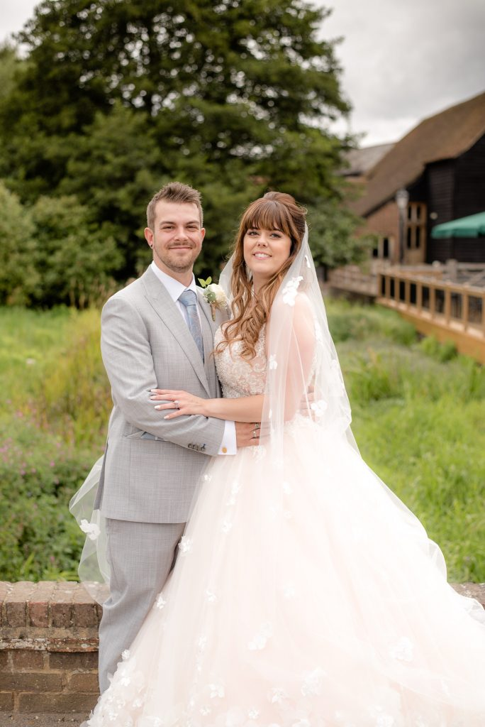 The groom and bride pose for a photo at Tewin Bury Farm