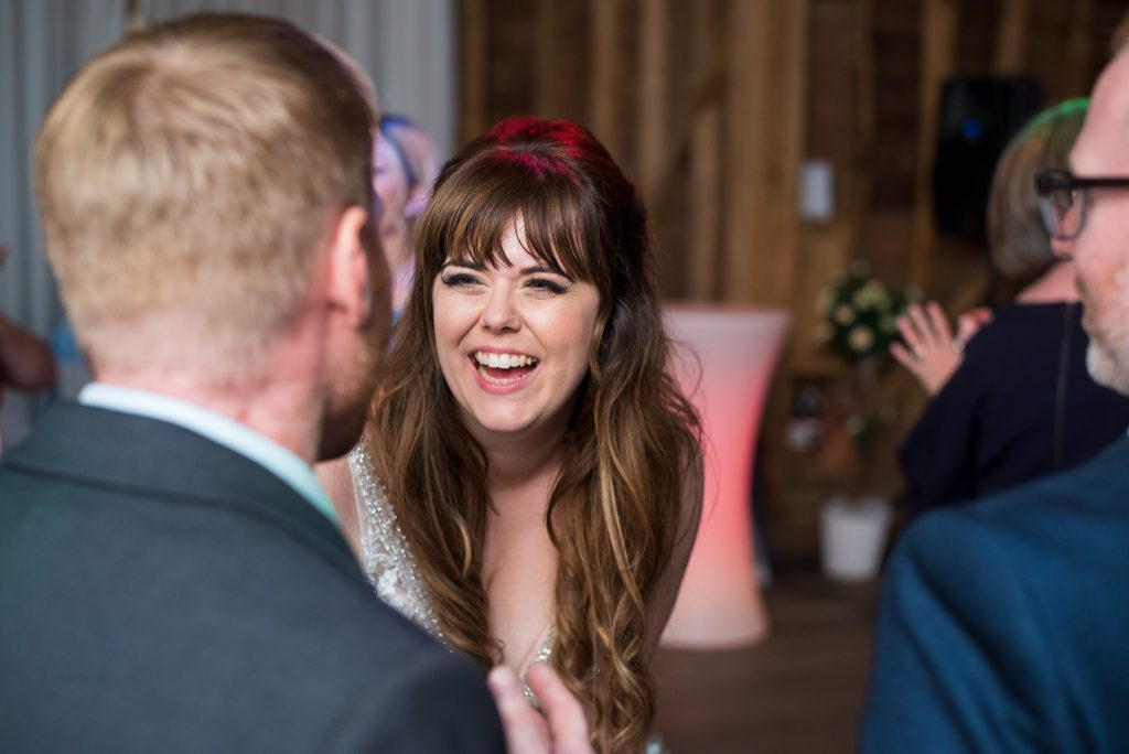 The bride laughs with wedding guests