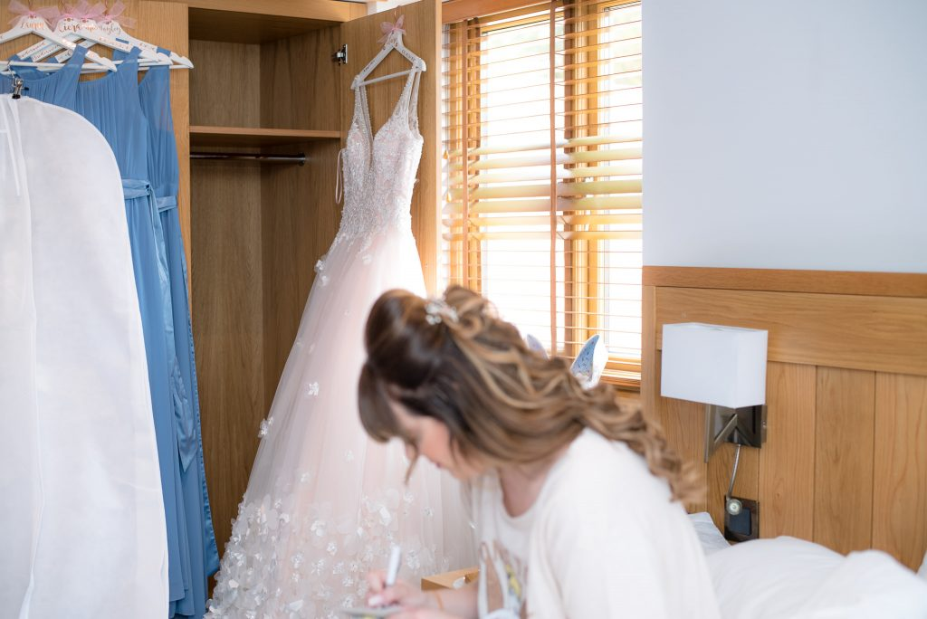 The bride writes a letter whilst her dress hangs in the background