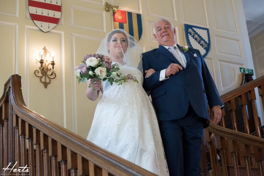 The father of the bride leads his daughter down the stairs