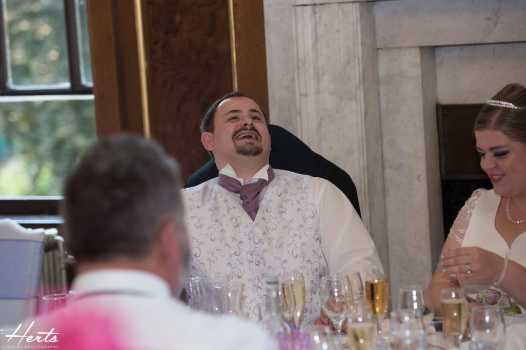 The groom laughs at the stories