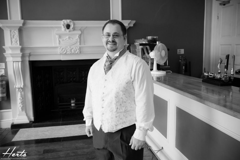 The groom stands beside the bar at Gosfield Hall