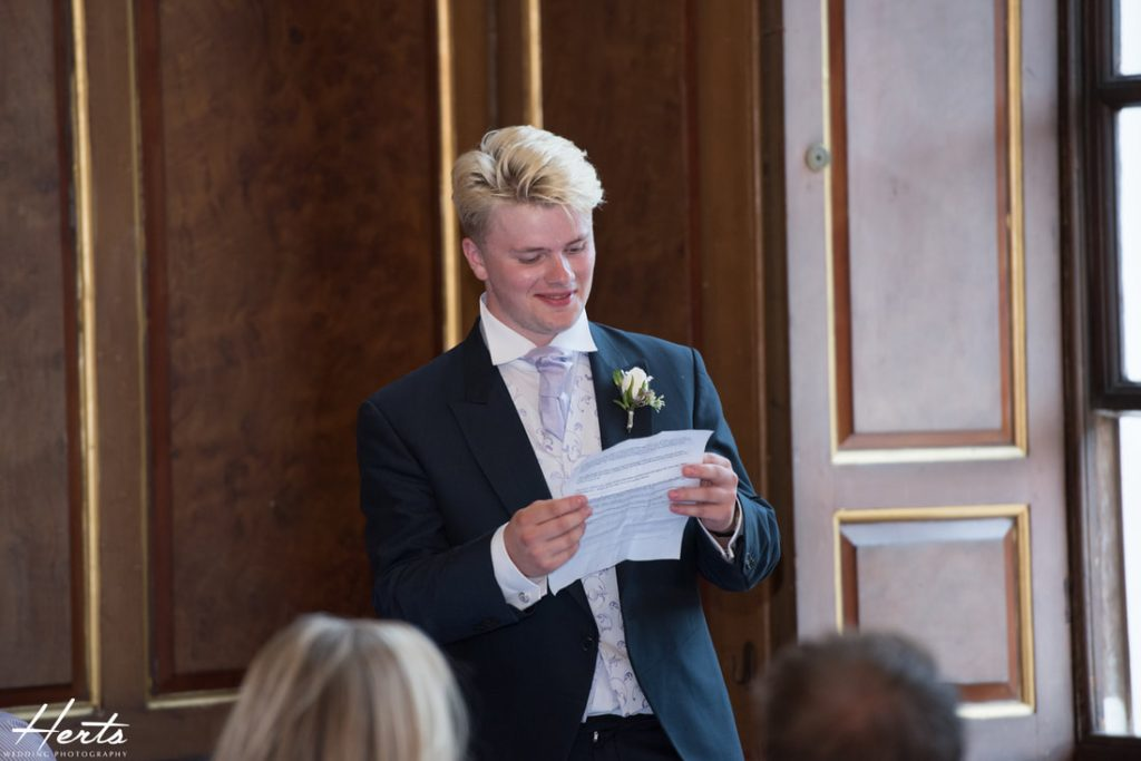 The grooms' cousin delivers his speech
