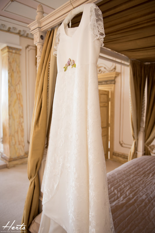 A handmade wedding dress hangs from the four poster bed