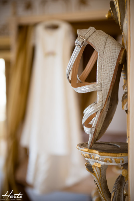 The brides shoes with the wedding dress in the background