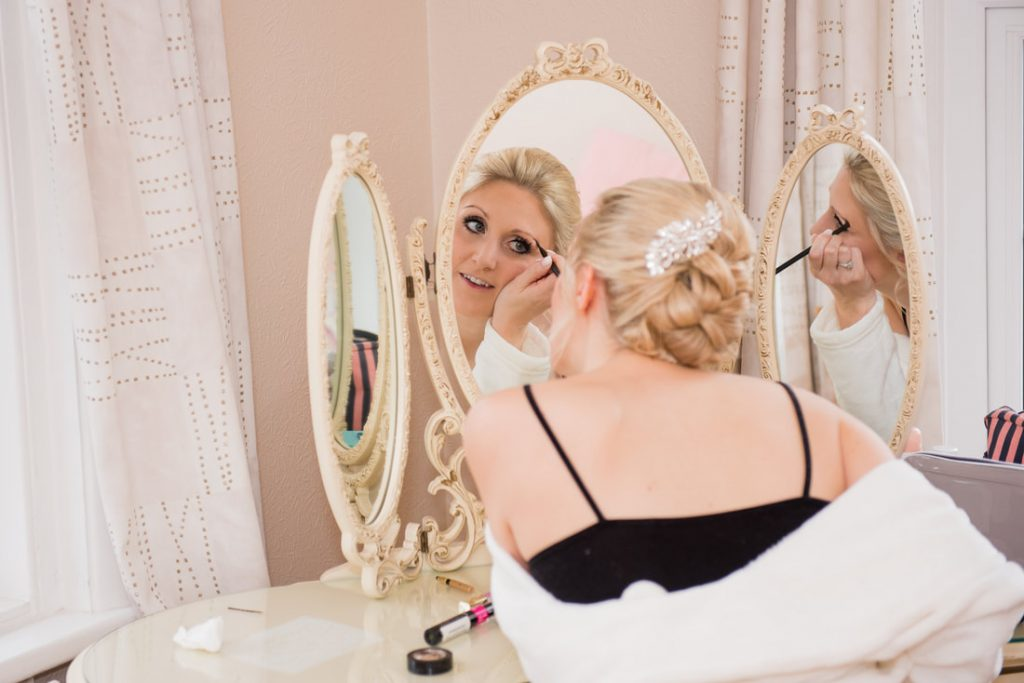 The bride applying makeup in a mirror