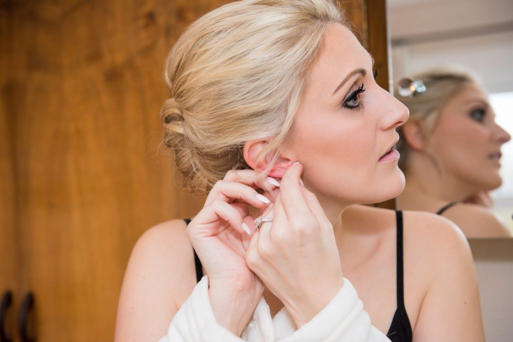 The bride putting on her earrings