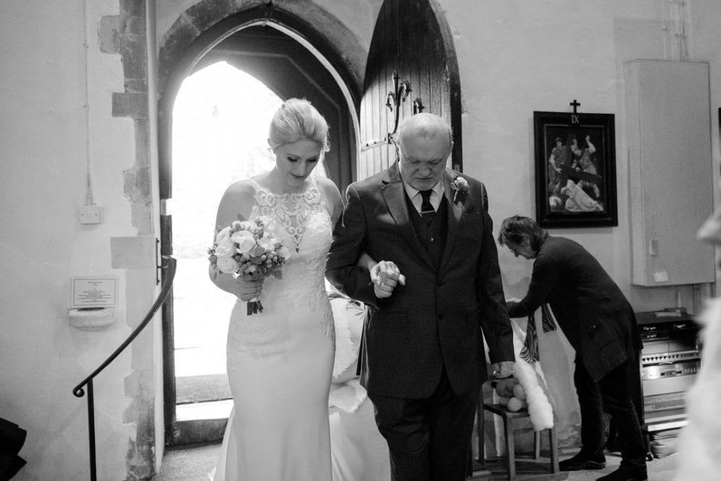 The father of the bride and bride entering the church