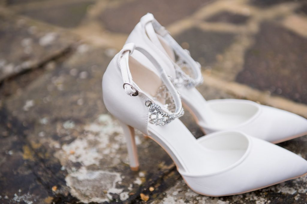 A close up of white wedding shoes