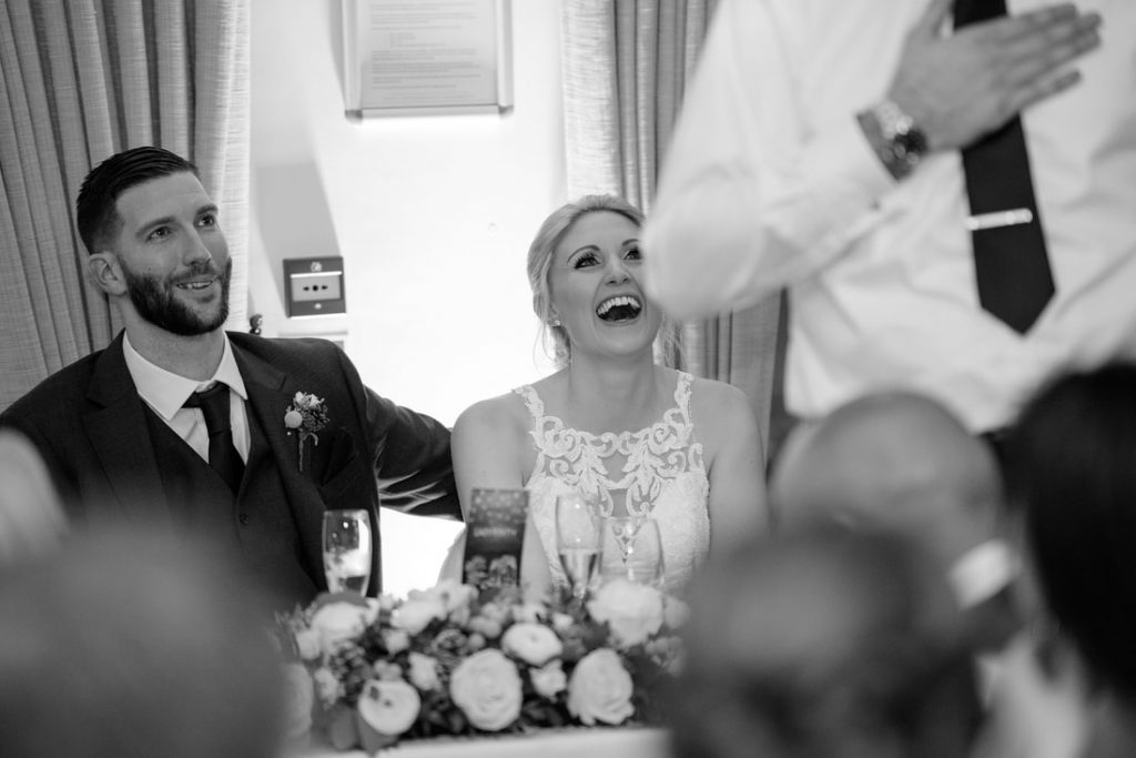 The bride and groom laughing at the speech