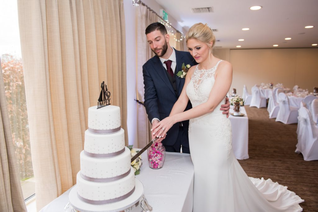 The bride and groom cutting the cake