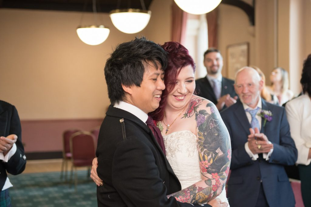 The bride and groom share a cuddle