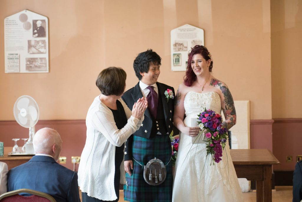 The registrar congratulating the bride and groom