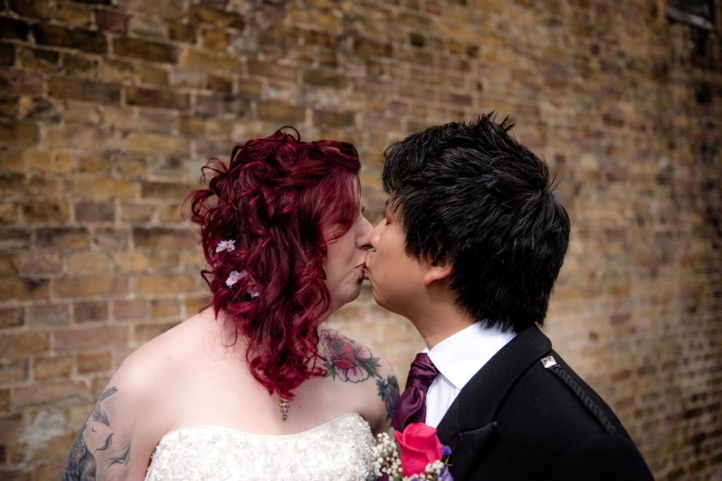The bride and groom kiss outside of Berkhamsted Town Hall