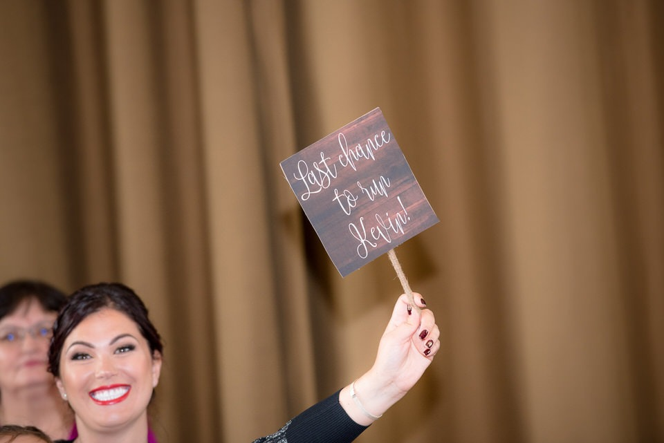 A wedding guest holding a humerous sign