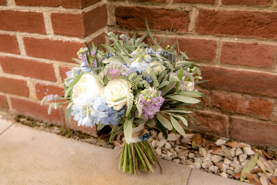 The brides bouquet of flowers by a red brick wall