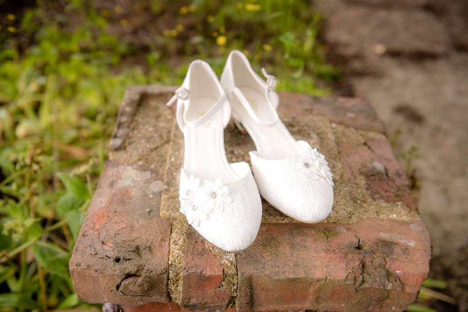 Wedding shoes sat on top of a wall