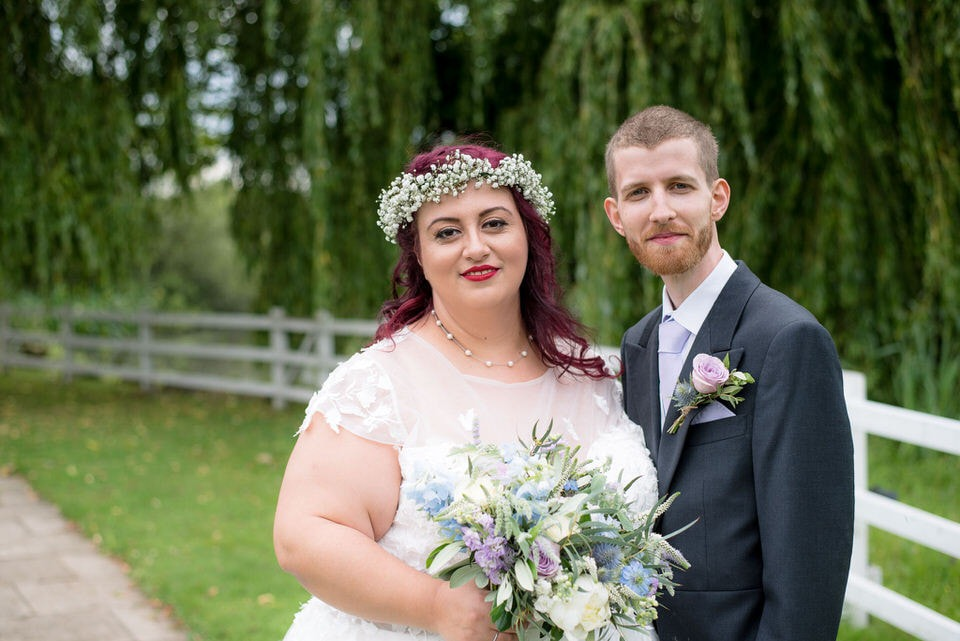 The bride and groom with a willow tree in the background