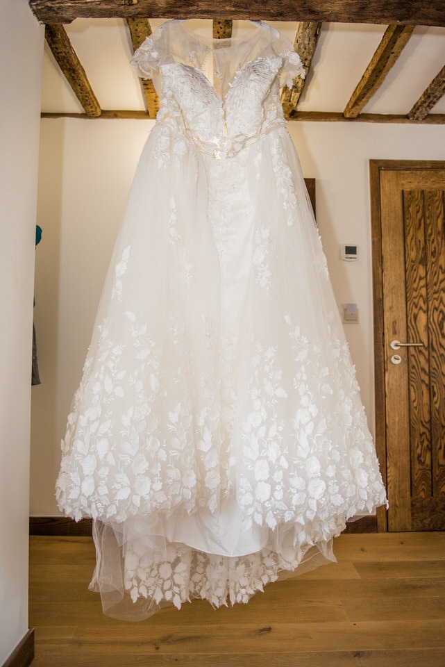 The wedding dress hanging from a wooden beam
