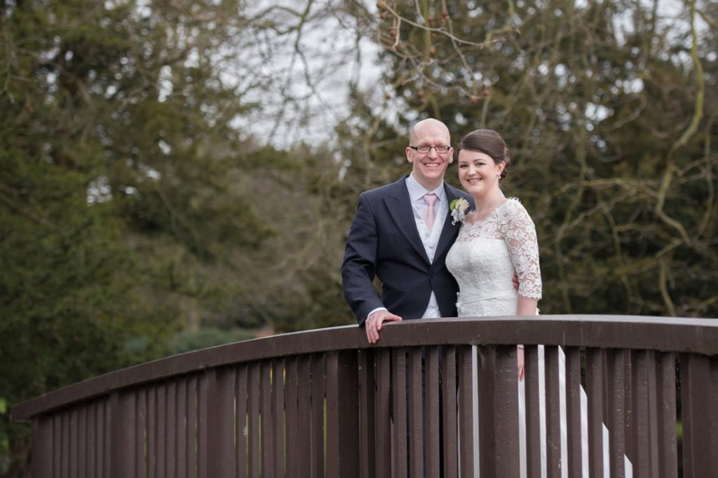 The bride and groom pictured on a wooden bridge