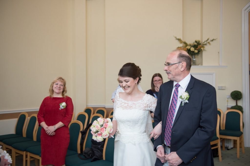 The bride is smiling radiantly as she walks into the ceremony room