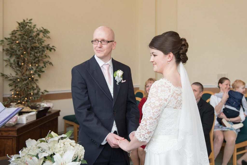 The bride and groom hold hands during the wedding ceremony