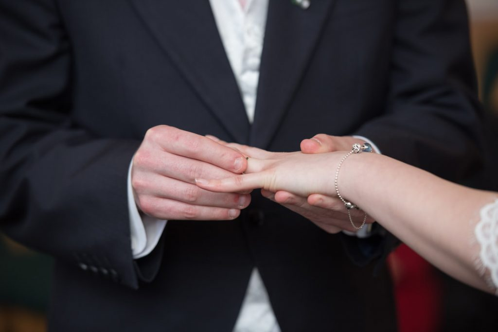 The groom places a wedding ring onto his bride
