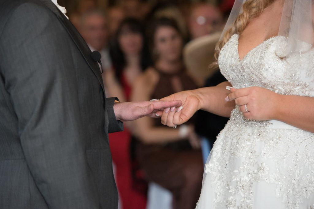 The bride places the wedding ring on the groom