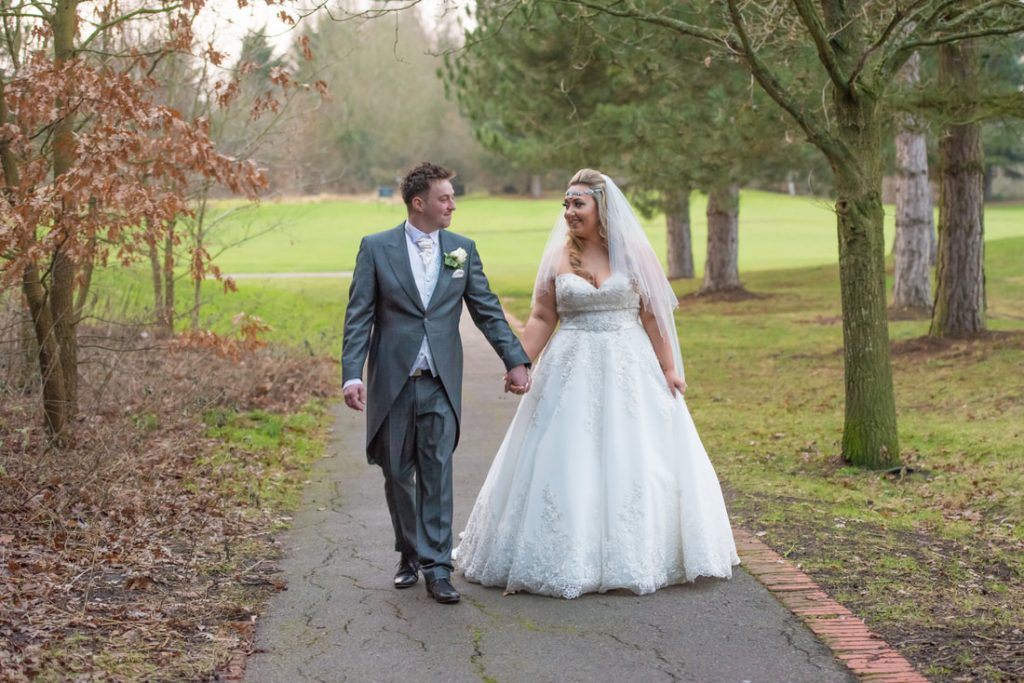 The bride and groom walk together at Essendon Country Club through the trees