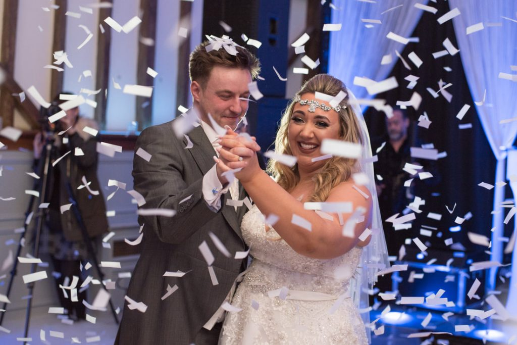 The bride and groom showered by a confetti cannon