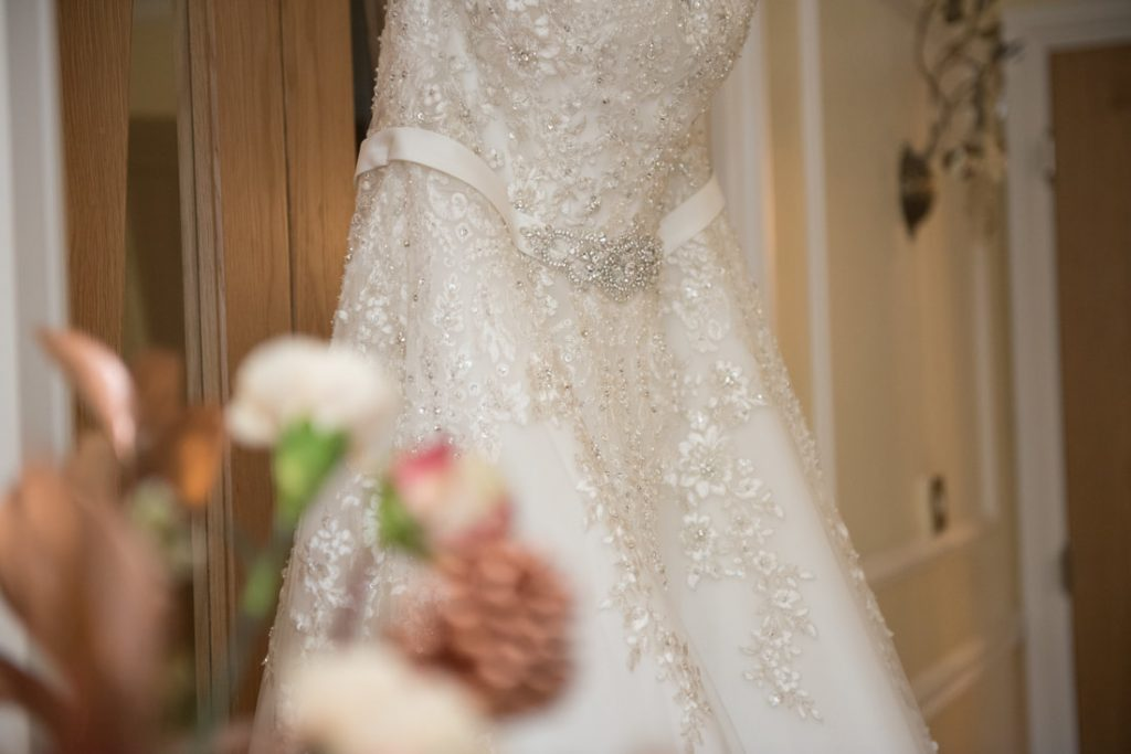 The stunning wedding dress hanging on a door frame