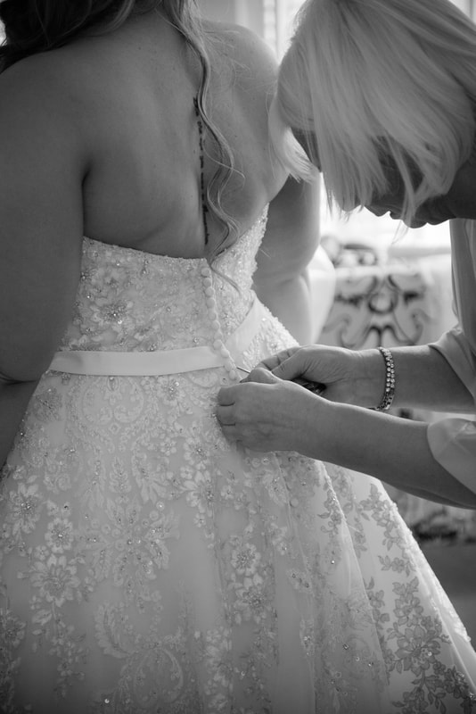 Mother of the bride buttons up the back of the wedding dress