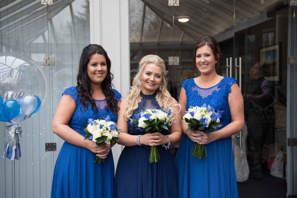 Three bridesmaids wearing stunning blue dresses