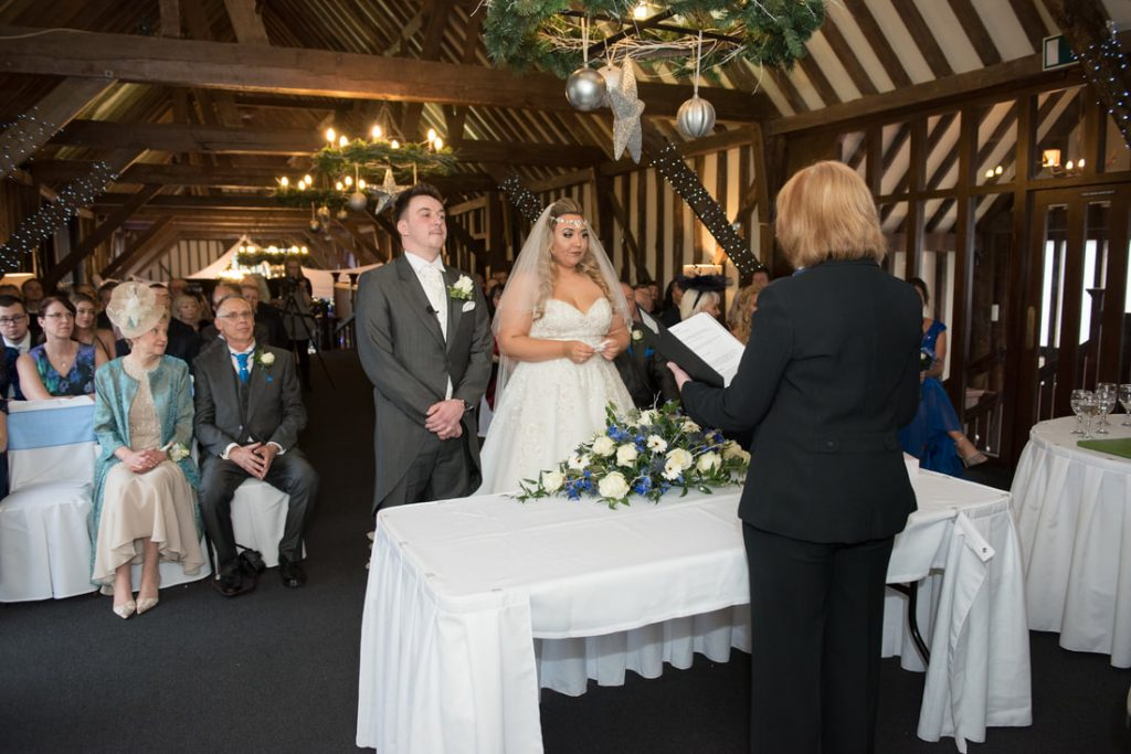 The bride and groom stand in front of their guests and the weddings registrar