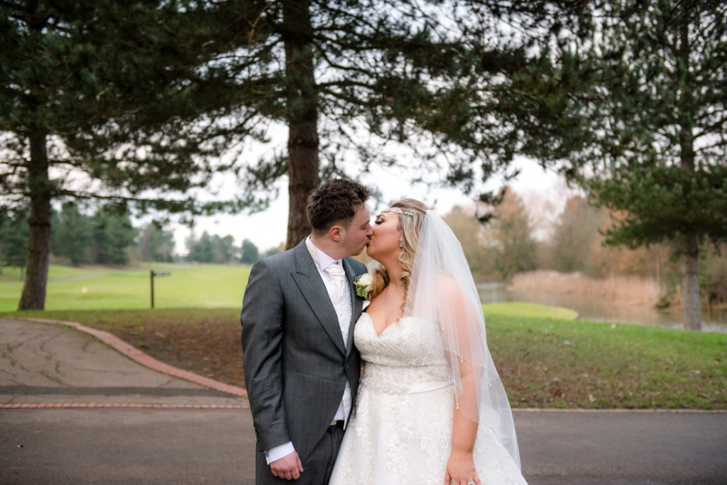 The bride and groom with Essendon Country Club Weddings Venue in the background besides the golf course