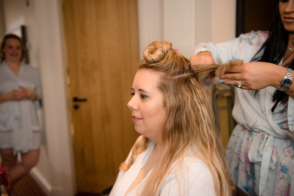 The bride is seated whilst her hair is styled