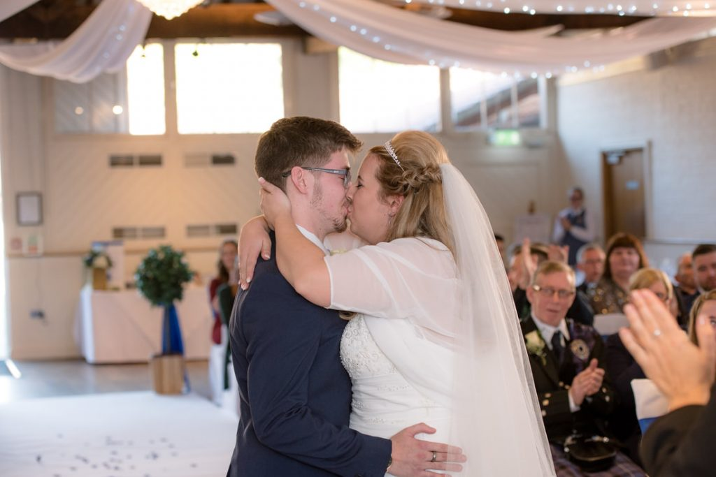 The bride and groom first kiss