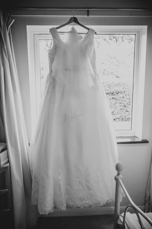 The wedding dress hanging against a window