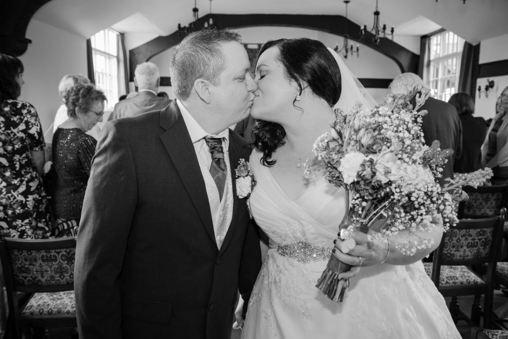 The bride and groom share a kiss before leaving