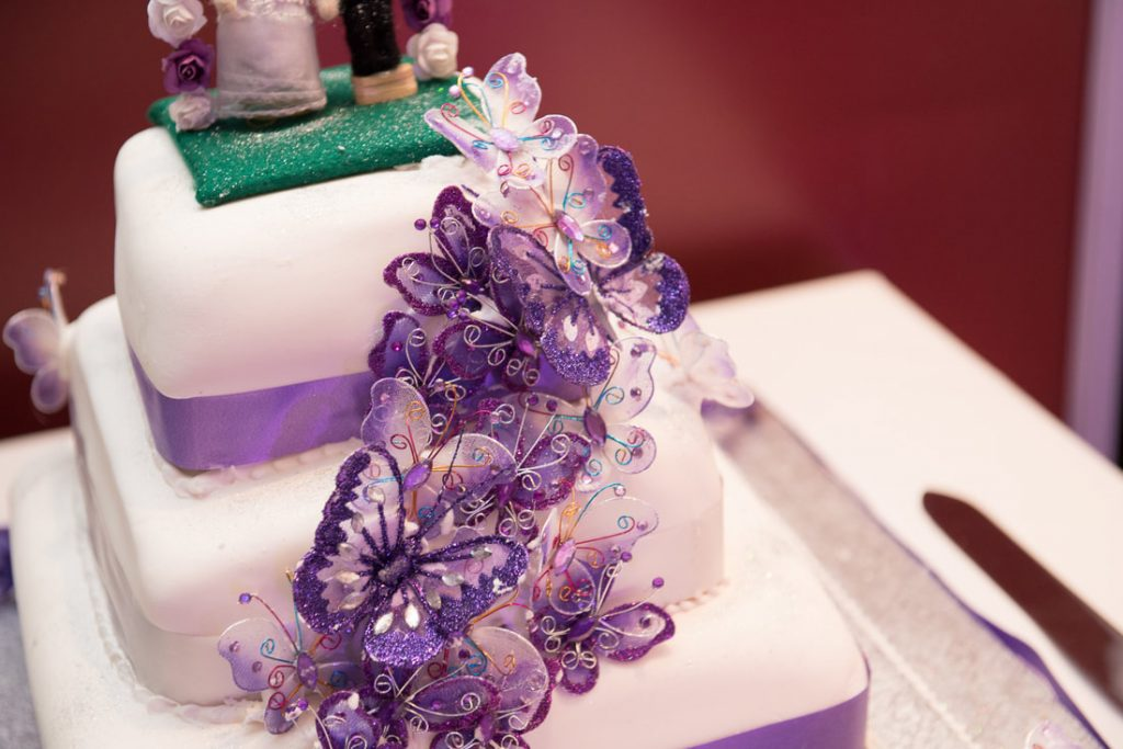 The tasty looking wedding cake with purple decorations