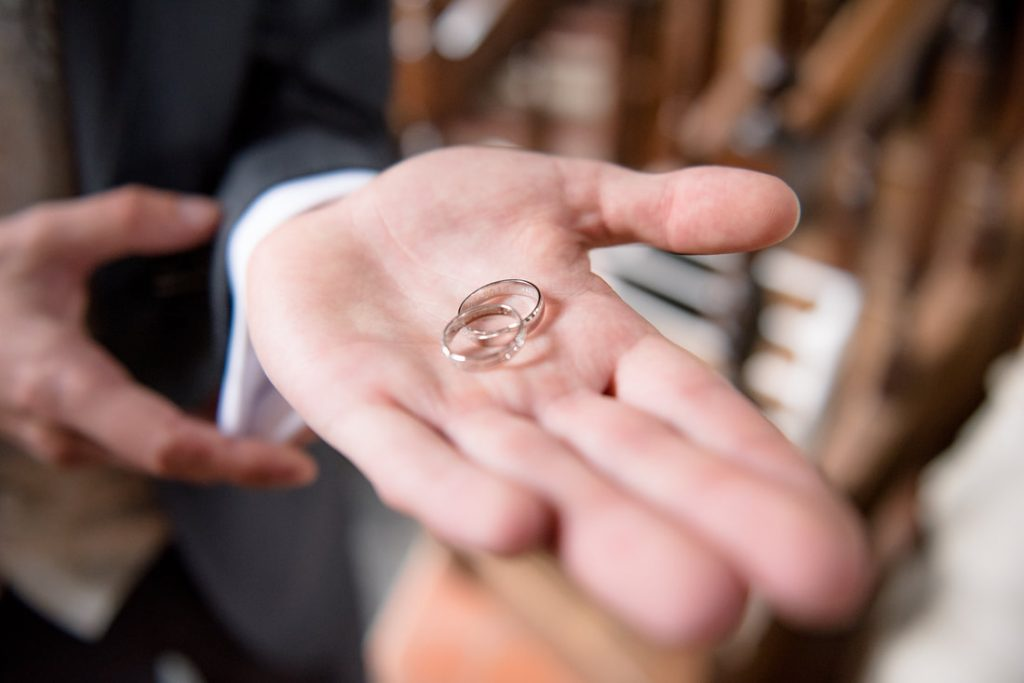 The groom holds the wedding rings in his hand