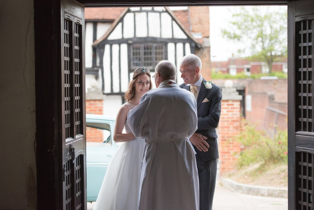 The bride, father and priest stand outside of the church