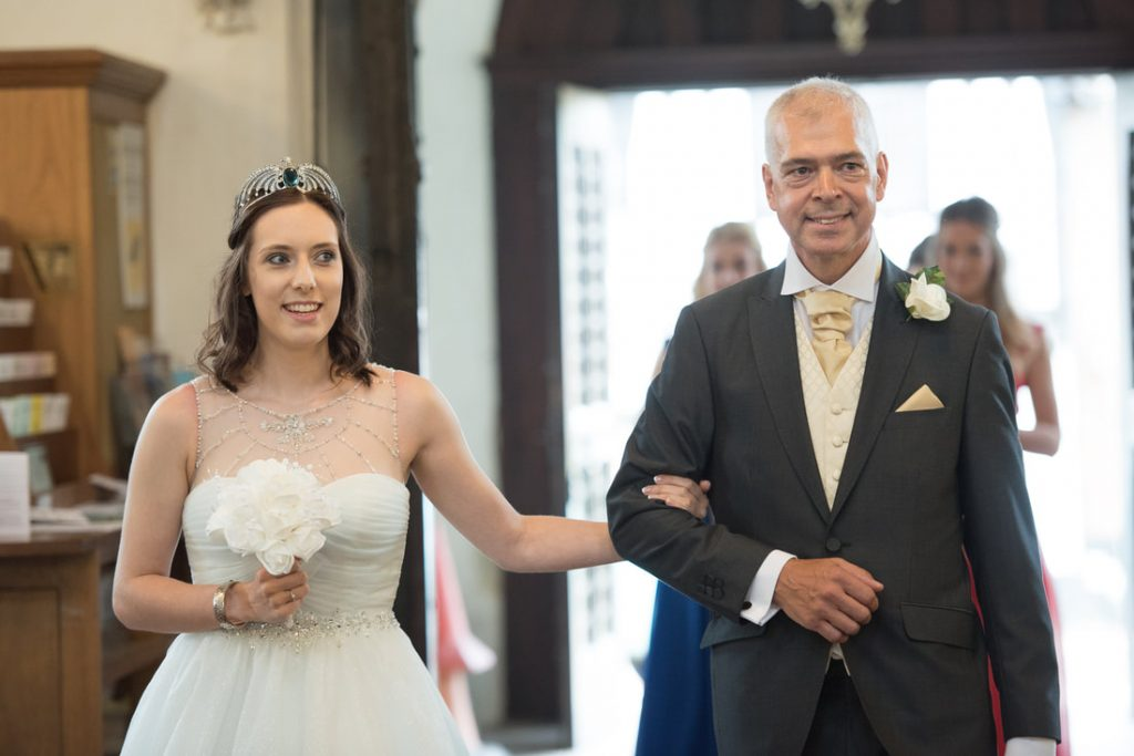 The bride and her father enter the church