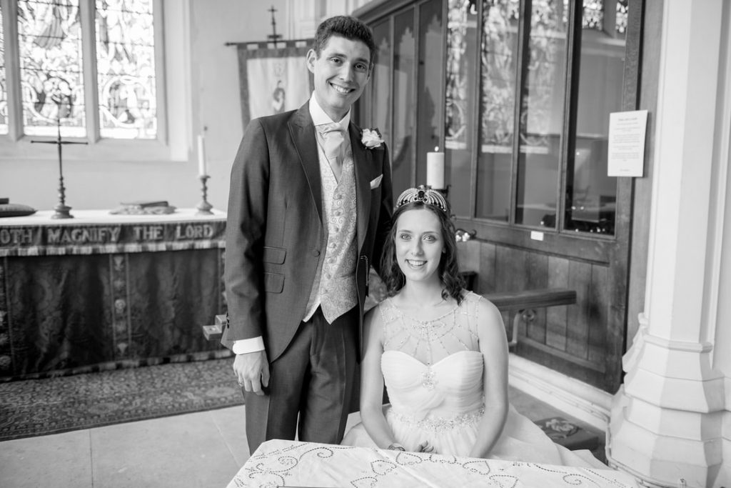 The bride and groom pose for the signing of the register