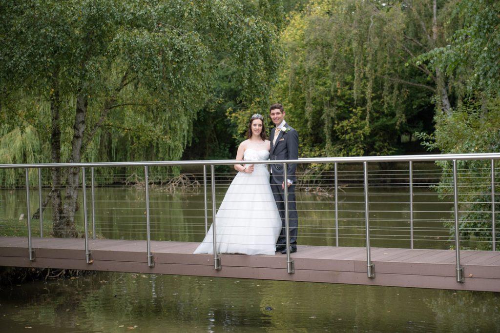 The bride and groom pose on a bridge at great hallingbury manor